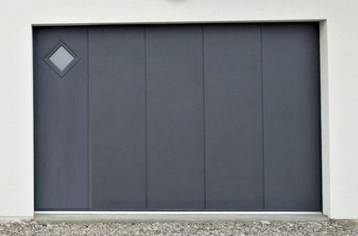 Porte de garage latérale en acier isolé 40mm. En version motorisée avec ouverture portillon séquentiel. Personnalisable avec motifs, hublots et laquage.